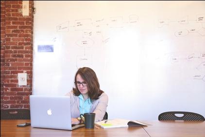 Frau sitzt vor dem Comupter am Bürotisch